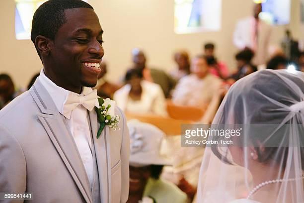 Bridegroom in church wedding ceremony smiling at bride