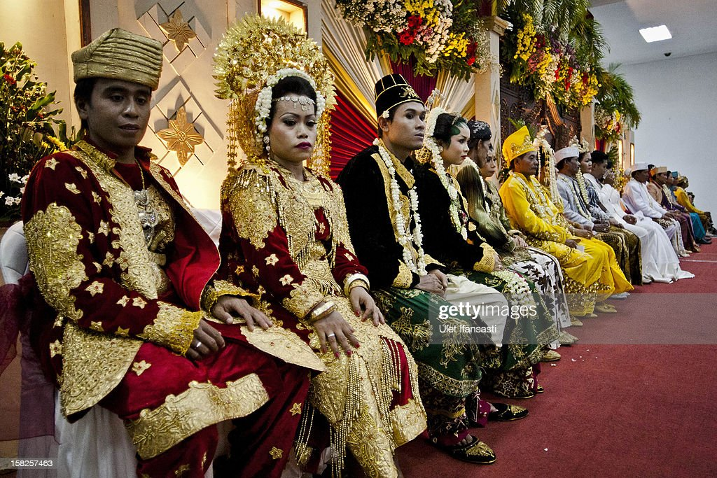 Brides and grooms sit lined up during a mass wedding ceremony on December 12, 2012 in Yogyakarta, Indonesia. Twelve couples participated in a mass wedding as today saw a surge in marriage across the globe to mark the once in a century date of 12/12/12.