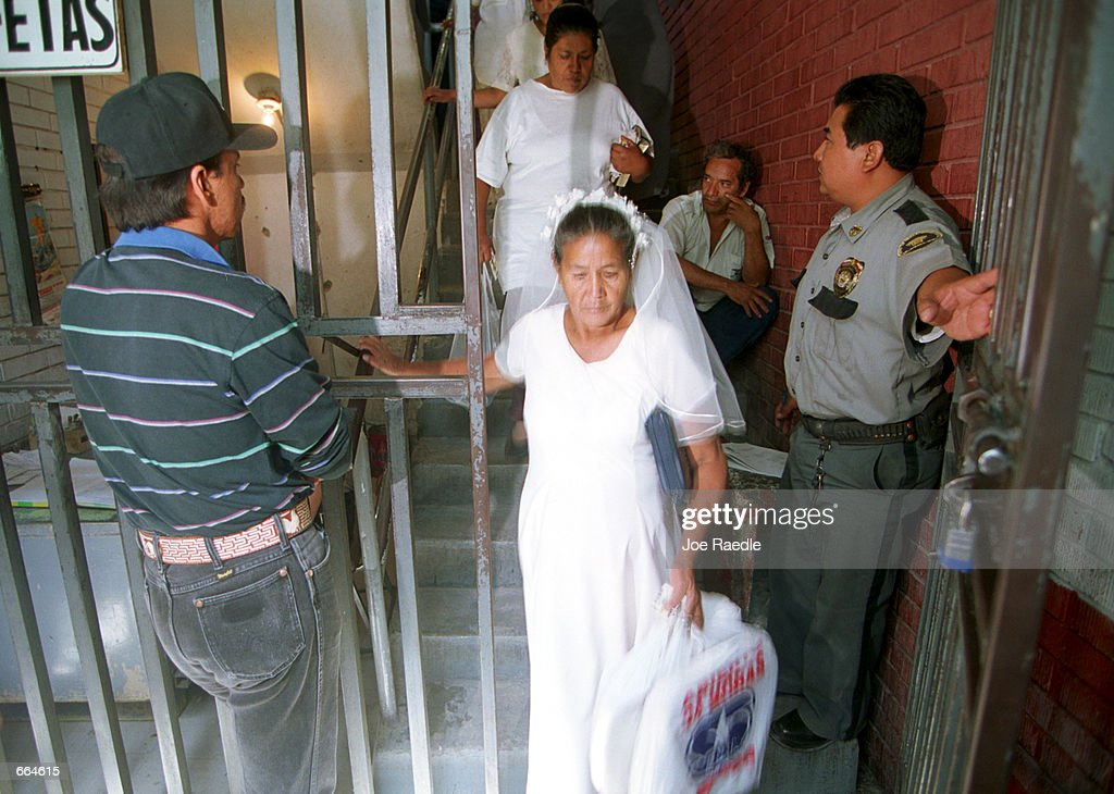 Brides are escorted through security gates into a prison October 2, 2000 in Ciudad Juarez, Mexico. Mexican law allows for inmates to marry inside prison walls. 5 couples, one current inmate and four former inmates were married by their church pastor. (Photo by Joe Raedle/Newsmakers) TO