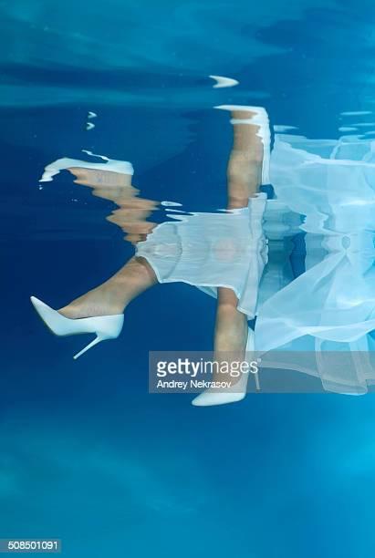 Bride's feet, underwater wedding in pool
