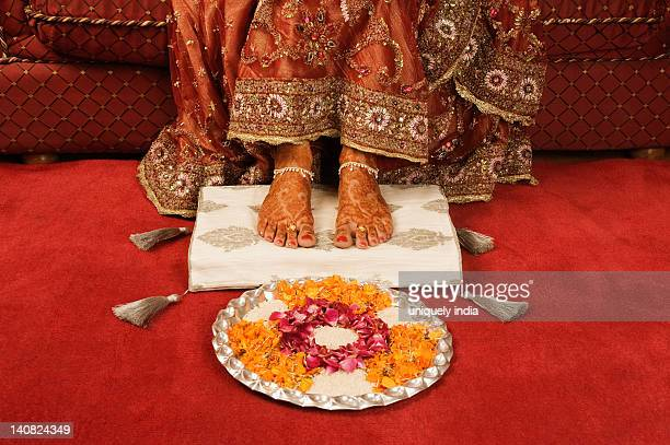 Bride's feet with henna decoration on a cushion with pooja thali