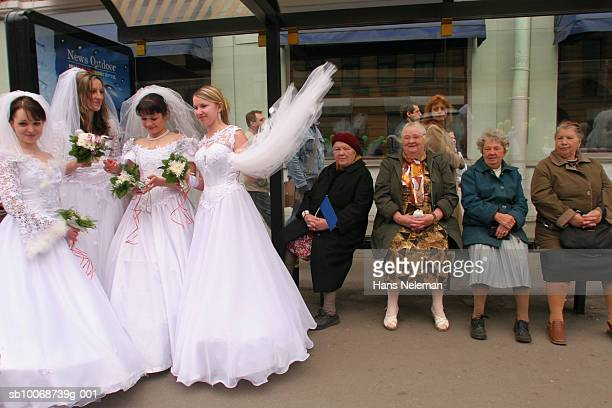 Brides waiting at bus stop in front of senior women