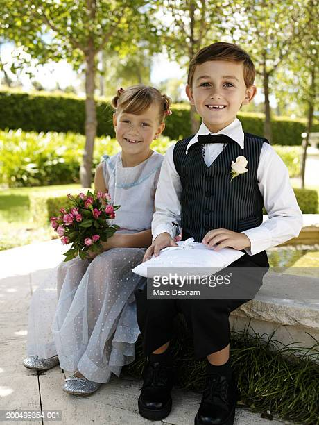 'Bridesmaid and pageboy(6-7)sitting by fountain, smiling, portrait'