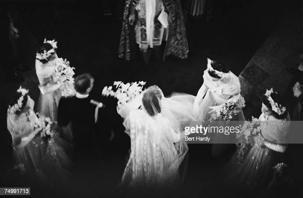 A bridesmaid arranging Princess Elizabeth's veil as she walks down the aisle with Lieutenant Philip Mountbatten at their wedding at Westminster Abbey...