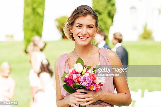 Bridesmaid Holding Bouquet Of Flowers At Garden Wedding