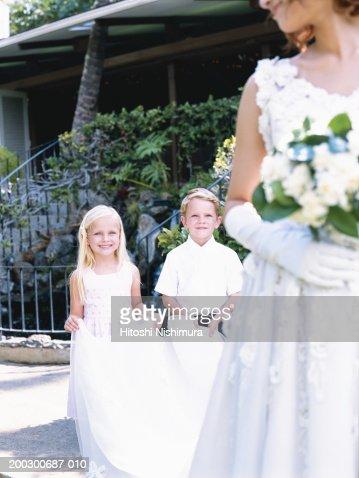 Bridesmaid holding bride's veil