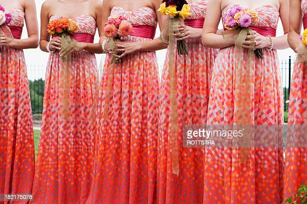 Bridesmaids wearing matching red patterned dresses