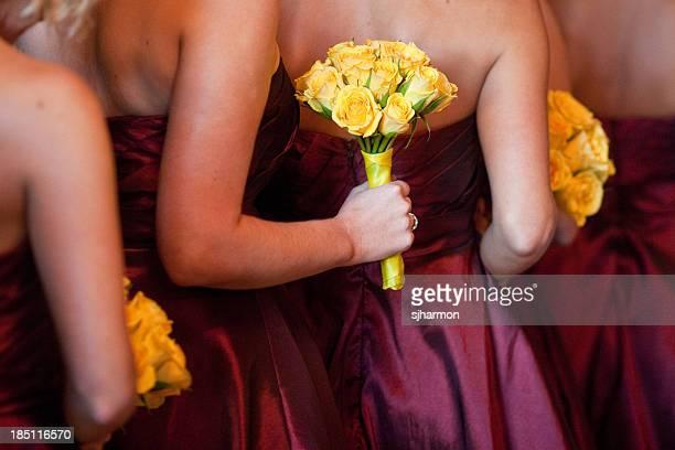 Brautjungfern mit gelben Blumensträuße stehen in Linie Church