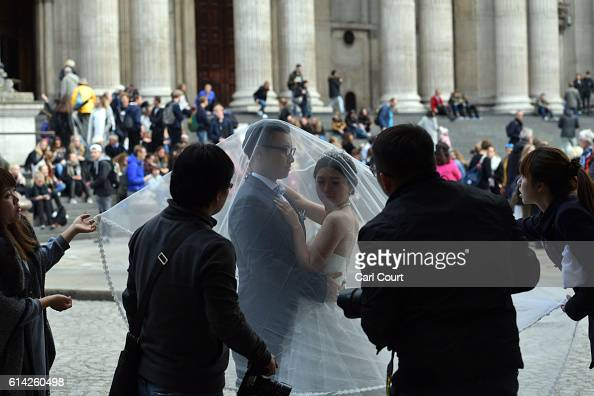 Bridetobe Echo Li and her fiance Charles Qian are assisted as they prepare to pose during a prewedding photography shoot at St Paul's Cathedral on...