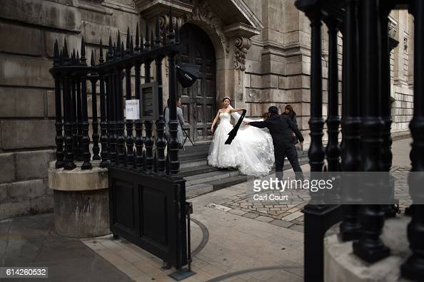 Bridetobe Echo Li passes her cardigan to an assistant during a prewedding photography shoot at St Paul's Cathedral on October 11 2016 in London...