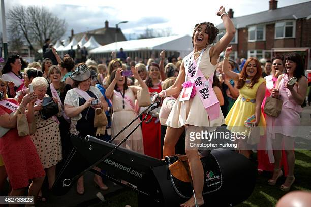 Bridetobe Gemma Blease enjoys a ride on a horse racing simulator as she and her hen party enjoy the atmosphere of Ladies Day at the Aintree Grand...