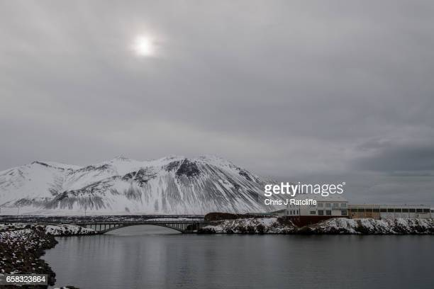 A bridge crosses water to a small industrial estate in the town of Borgarnes at the foot of mountains on March 27 2017 at Borgarnes Iceland Iceland's...