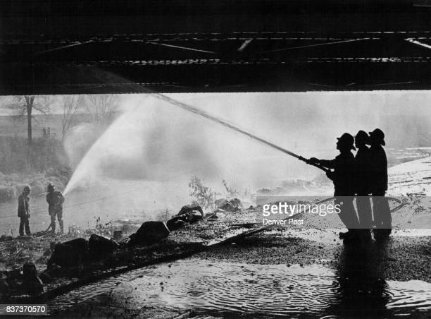 Bridge Damaged By Smoldering Fire Firemen spray water onto the Burlington Northern Railroad bridge at East 44th Avenue and Washington Street after...