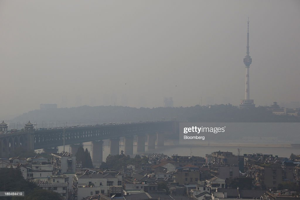 A bridge on the Chang Jiang river, left, and the television tower, right, stand shrouded in a haze in Wuhan, China, on Sunday, Oct. 20, 2013. China's economic expansion accelerated to 7.8 percent in the third quarter from a year earlier, the statistics bureau said Oct. 18, reversing a slowdown that put the government at risk of missing its 7.5 percent growth target for 2013. Photographer: Tomohiro Ohsumi/Bloomberg via Getty Images
