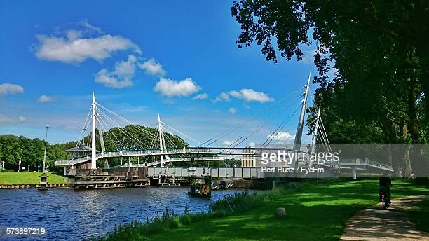 Bridge Over Canal By Grassy Field Against Cloudy Sky