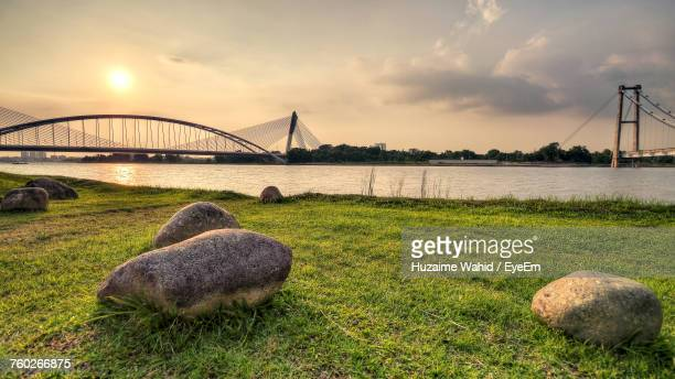Bridge Over River Against Cloudy Sky