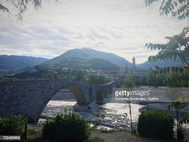 Bridge Over River By Mountains Against Sky
