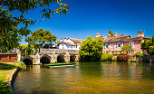 A stone bridge spans the River Avon Christchurch Dorset England on a hot summer day