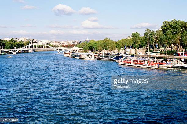 A bridge over the Seine River with boats along the shore in Paris, France.
