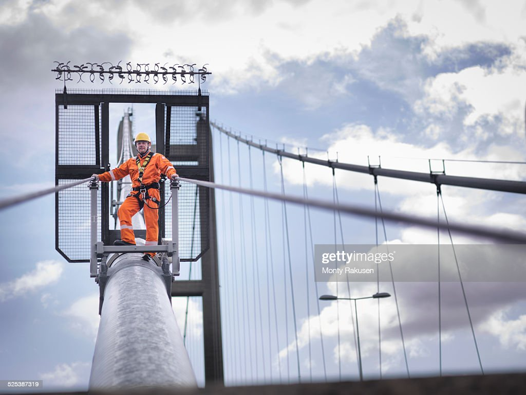 Bridge worker on cable of suspension bridge. The Humber Bridge, UK was built in 1981 and at the time was the worlds largest single-span suspension bridge