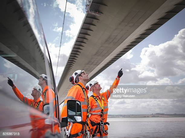 Bridge workers and support truck under suspension bridge. The Humber Bridge, UK was built in 1981 and at the time was the worlds largest single-span suspension bridge
