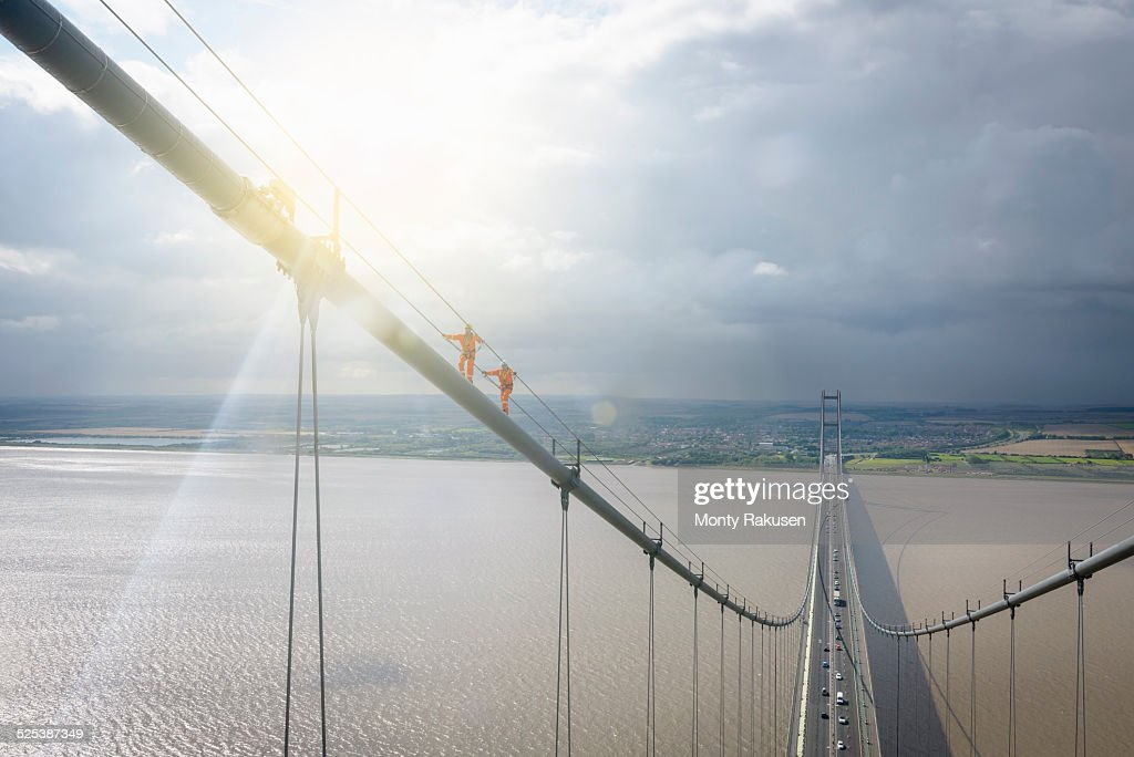 Bridge workers walking on cable of suspension bridge under bright sunlight. The Humber Bridge, UK was built in 1981 and at the time was the worlds largest single-span suspension bridge