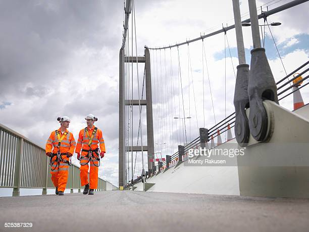 Bridge workers walking on parapet of suspension bridge. The Humber Bridge, UK was built in 1981 and at the time was the worlds largest single-span suspension bridge