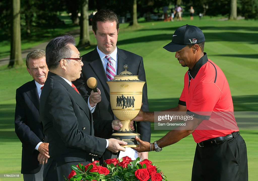 Bridgestone Global CEO and Chairman of the Board Masaaki Tsuya (L) poses with Tiger Woods and the Gary Player Cup Trophy during the Final Round of the World Golf Championships-Bridgestone Invitational at Firestone Country Club South Course on August 4, 2013 in Akron, Ohio.