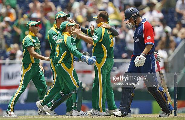 England's Andrew Strauss walks back to pavillion after his dismissal as South Africa' cricketers celebrates his wicket during their ICC World Cup...