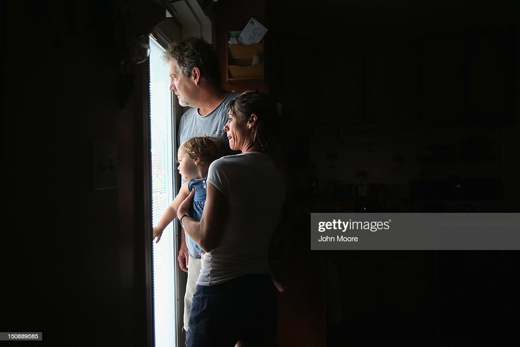 Bridgette Mooney, her daughter Skyler, 15 months, and husband Kevin watch from their home as Hurricane Isaac lashes their property with rain on August 28, 2012 in Kiln, Mississippi. Many residents of the community, which suffered severe damage during Hurricane Katrina in 2005, decided to stay home and ride out the storm.