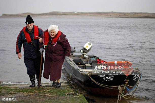 Bridgie O'Malley is helped by her son Joe from the small boat that he operates as a passenger ferry on Achill Sound to the island of Inishbiggle...