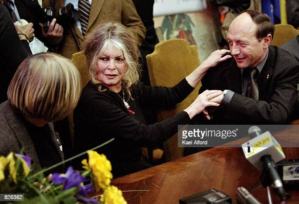 Bridgitte Bardot reaches out to Traian Basescu the mayor of Bucharest Romania after signing an agreement with the city March 1 2001 regarding the...