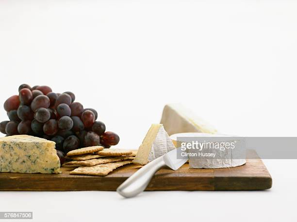 Brie cheese, blue cheese, crackers and grapes on a cutting board