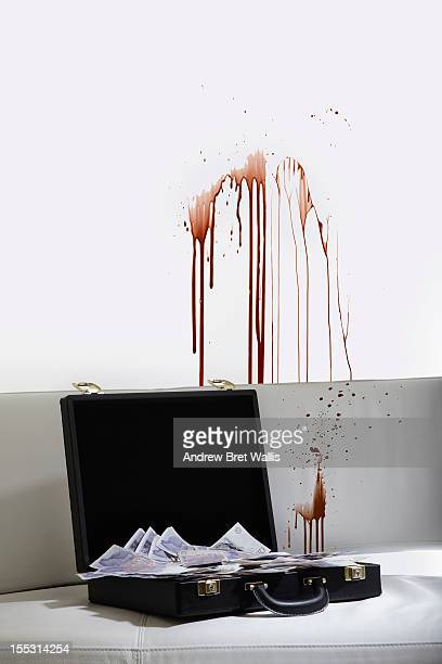 A briefcase of money and a blood stained wall