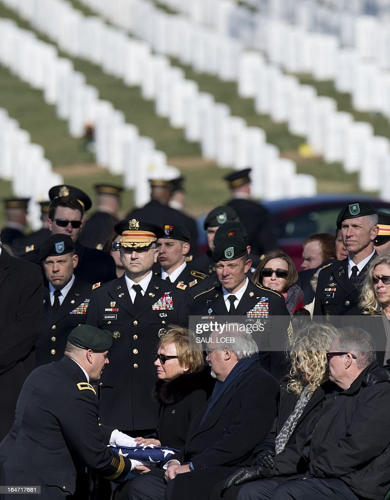 Brig. General Christopher Haas, commander of the US Special Forces Command in Fort Bragg, North Carolina, presents a flag to Helen Keiser-Pedersen, mother of US Army Captain Andrew Pedersen-Keel, during a burial service in Section 60 at Arlington National Cemetery in Arlington, Virginia, March 27, 2013. Pedersen-Keel, 28, was killed March 11 during an attack on a police station in Afghanistan. AFP PHOTO / Saul LOEB