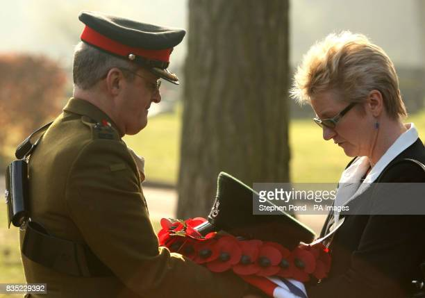 Brigadier Barry passes a hat and union flag to mother Janet Gunn during the cremation of her son Rifleman Jamie Gunn after the funeral service at St...