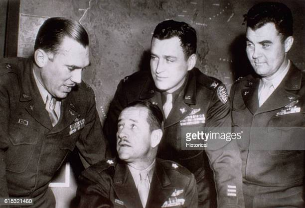 Brigadier General Roger Ramey seated talks with his atomic bomb testing staff memebers left to right Colonel Alfred F Kalberer Colonel William...