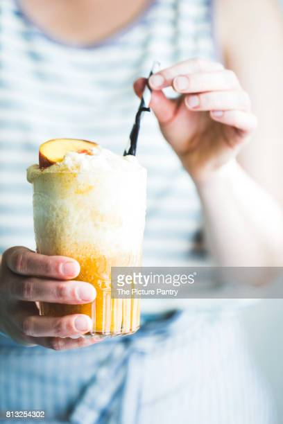 Bright and colorful Ice cream float being held in a womans hands