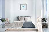 Beige blanket on king-size bed against wall with simple painting in bright bedroom interior with plants