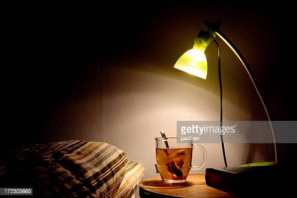 Bright bedside lamp with a clear cup of tea next to the bed