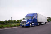 Bright blue modern popular huge comfortable big rig semi truck for professional commercial freights haul reefer semi trailer for food delivery moving on wide straight road with green trees on the side