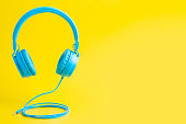 Minimalist bright composition of blue headphones on vibrant yellow background.