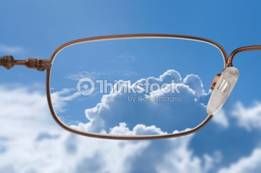 Bright blue sky with white clouds through a glasses lens : Stock Photo