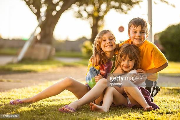Brilhante de cor três crianças agrupados sorridente Neighborhood Lawn mais suave