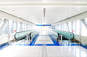 an empty white, bright corridor with two moving walkways, white, blue and green colors, long exposure Dubai, United Arab Emirates