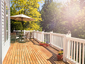 Afternoon bright daylight on outdoor home cedar deck with furniture and open umbrella. Light effect applied to image. Horizontal layout.