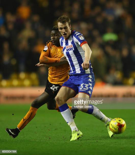 Bright Enobakhare of Wolverhampton is held off by Dan Burn of Wigan during the Sky Bet Championship match between Wolverhampton Wanderers and Wigan...