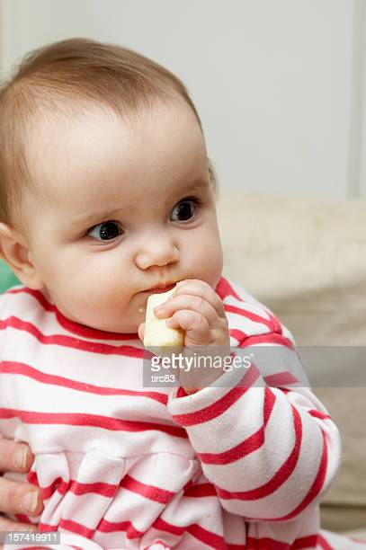Bright eyed one year old girl eating banana
