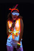 Stylish bright young woman singing in darkness under UV light