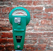 A bright green parking meter on a brick background